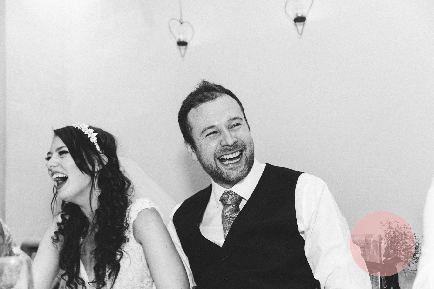 Bride and groom laughing at the best mans speech