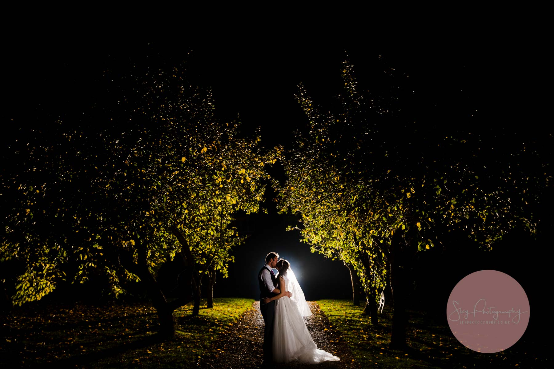 Beautiful image of the couple standing under the trees at Dodmoor house a signature wedding shot