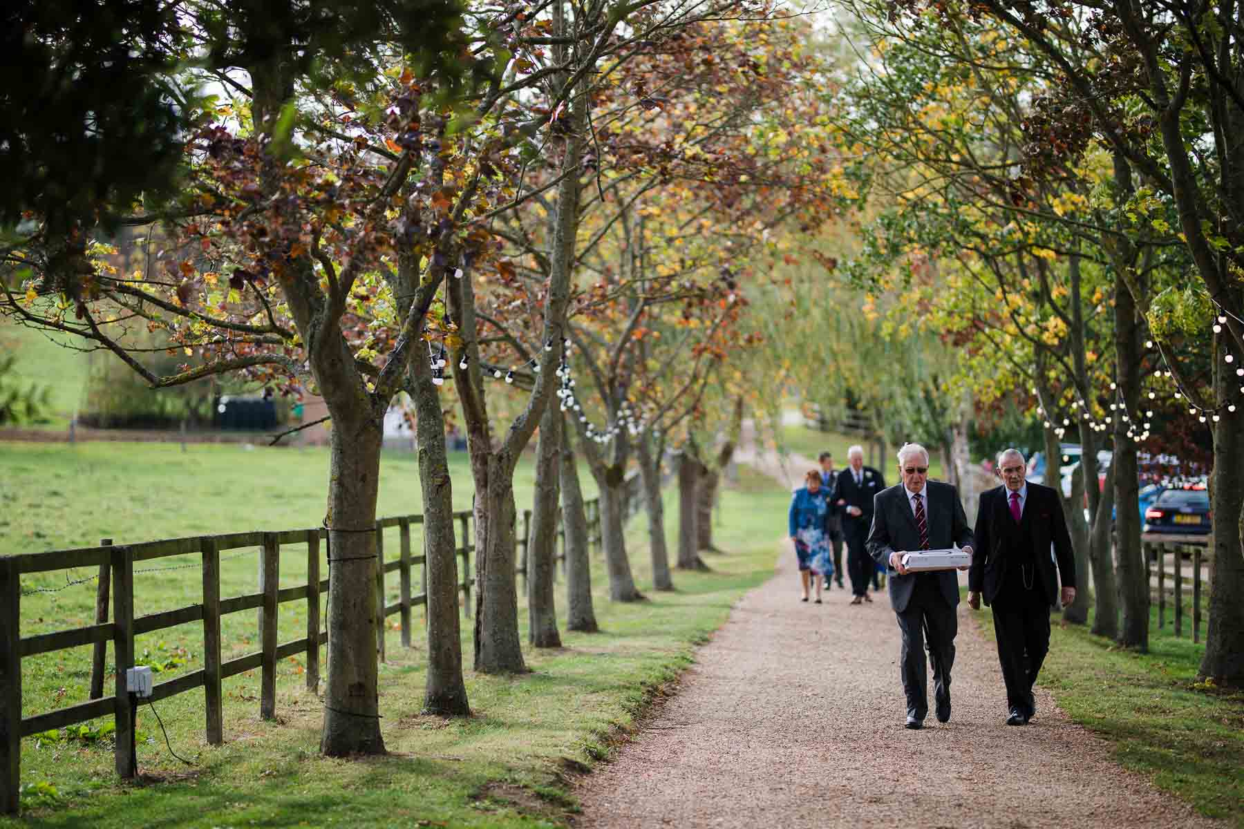 Guests walking up the tree lined drive of Wood Farm