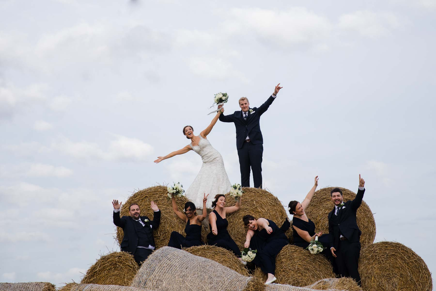 Wedding Party standing on the hay bales at wood farm