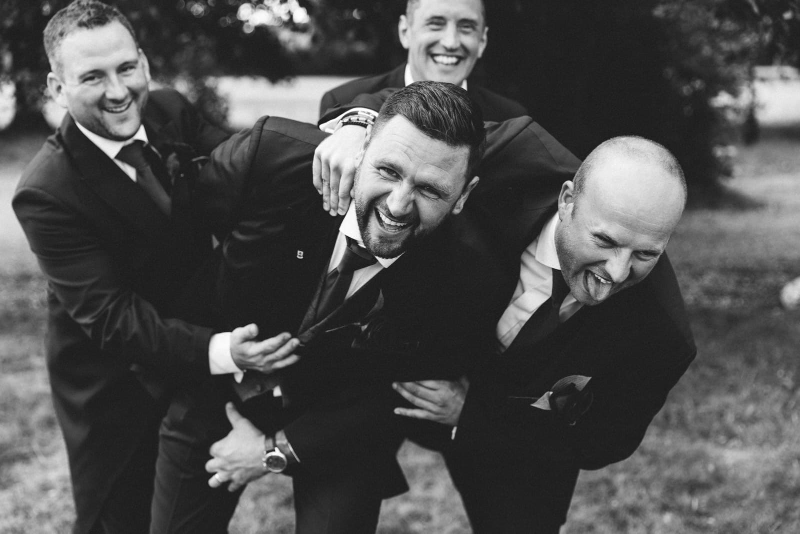 groomsmen playing with the groom and grabbing him