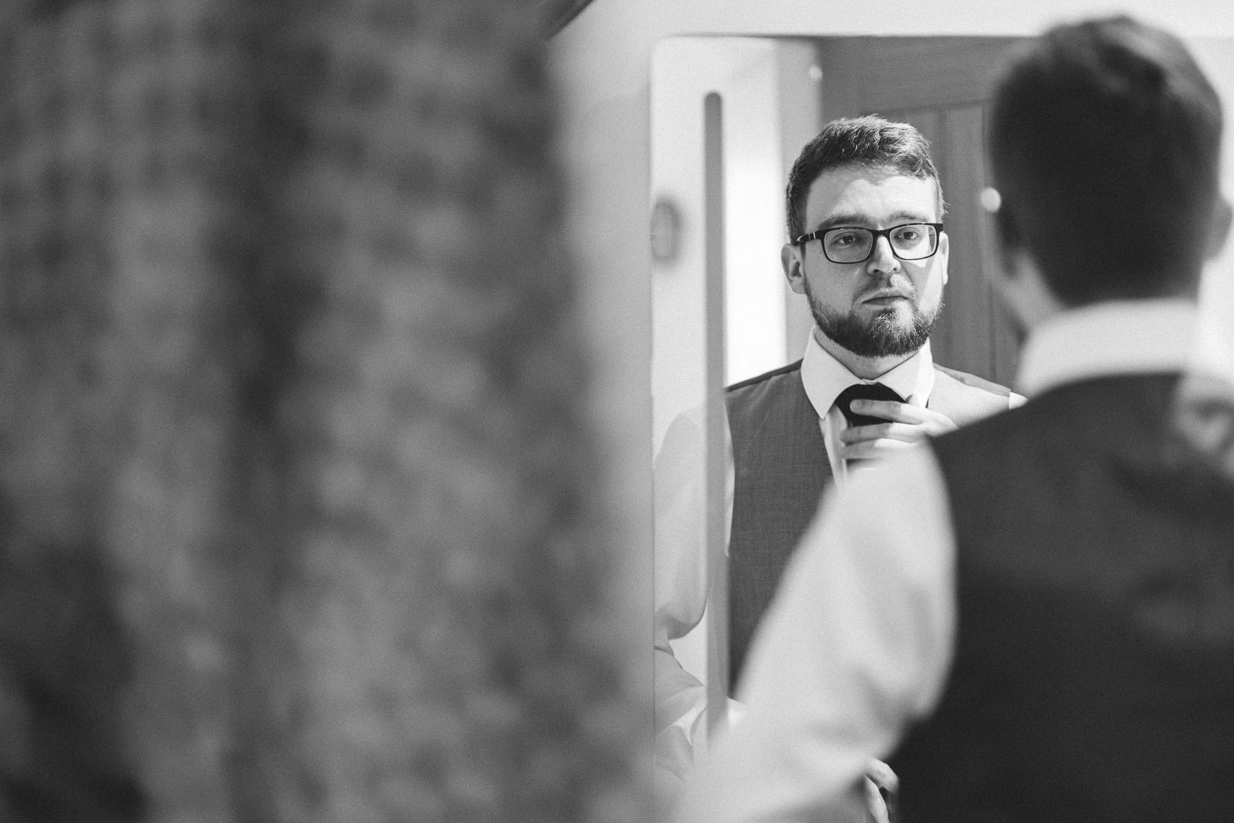 Groom looking in the mirror getting ready for his wedding in kettering