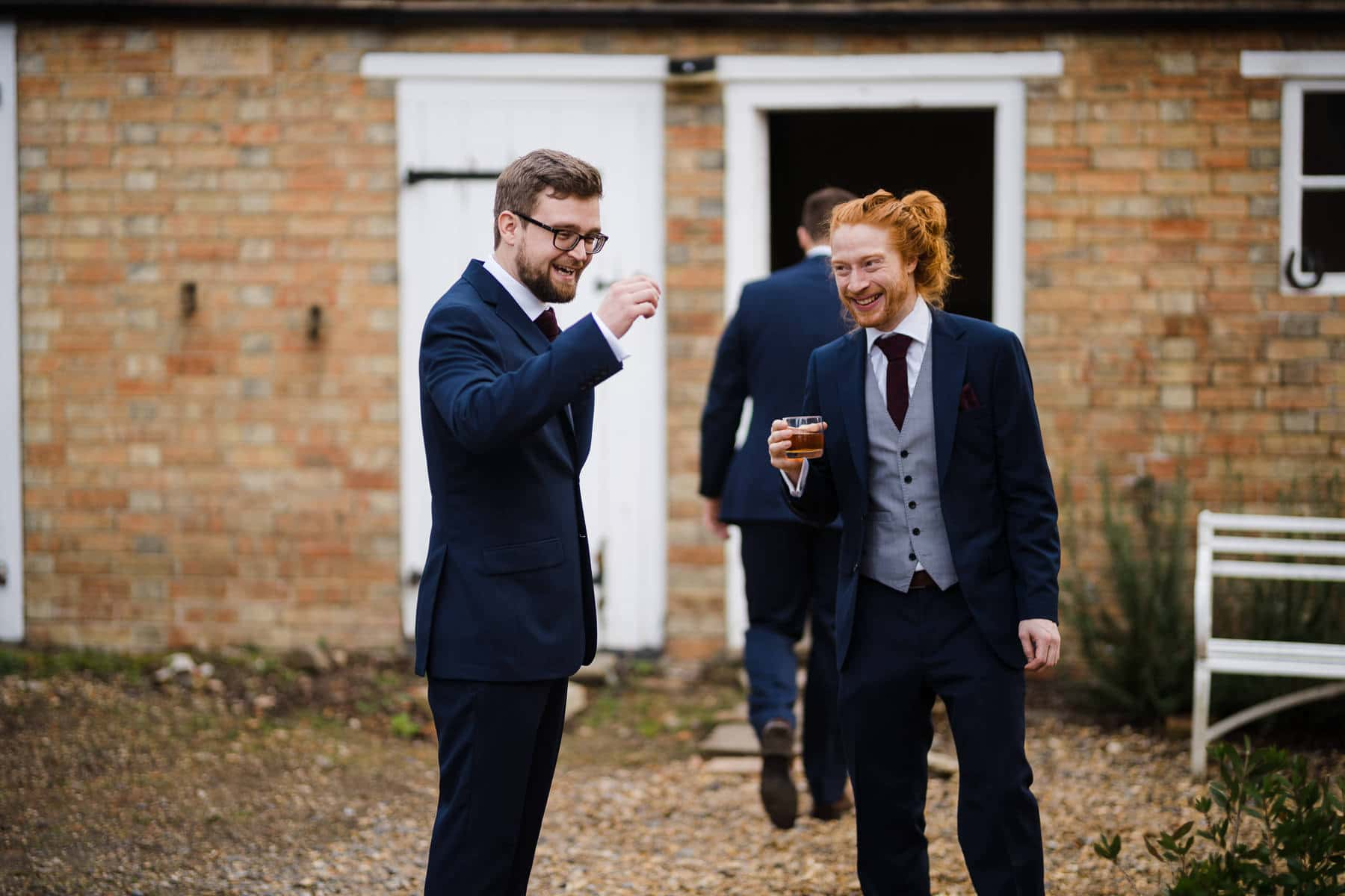 Groom and groomsmen sharing a laugh and wiskey