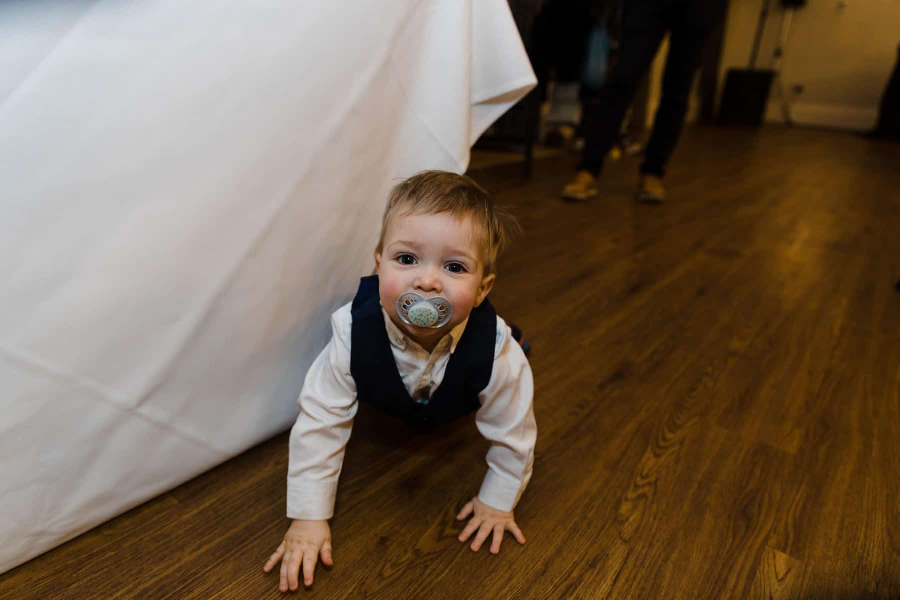 Baby hiding under the wedding head table