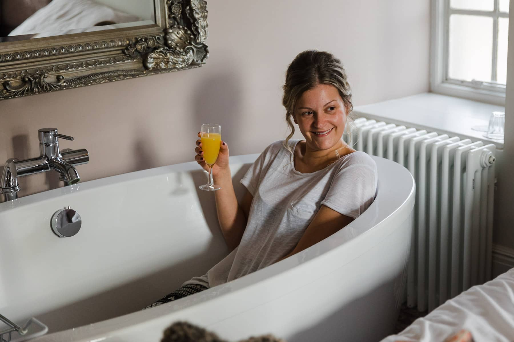 Bridesmaid drinking champagne in the bath at barton hall