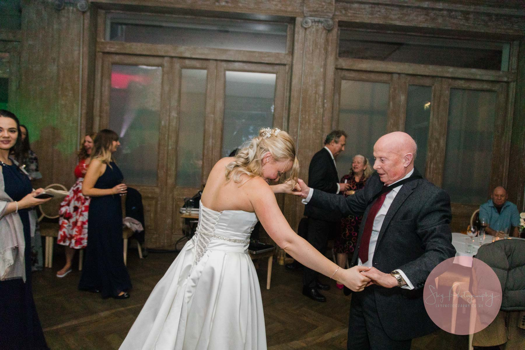 Bride and Grandfather dance next to a band