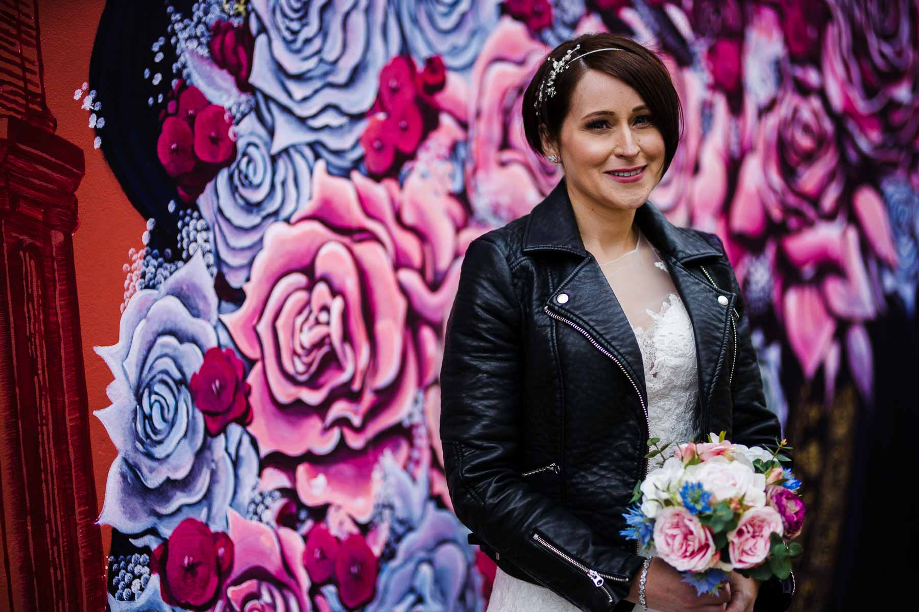 Buckinghamshire wedding photography of Claire in her leather jacket standing next to grafitti