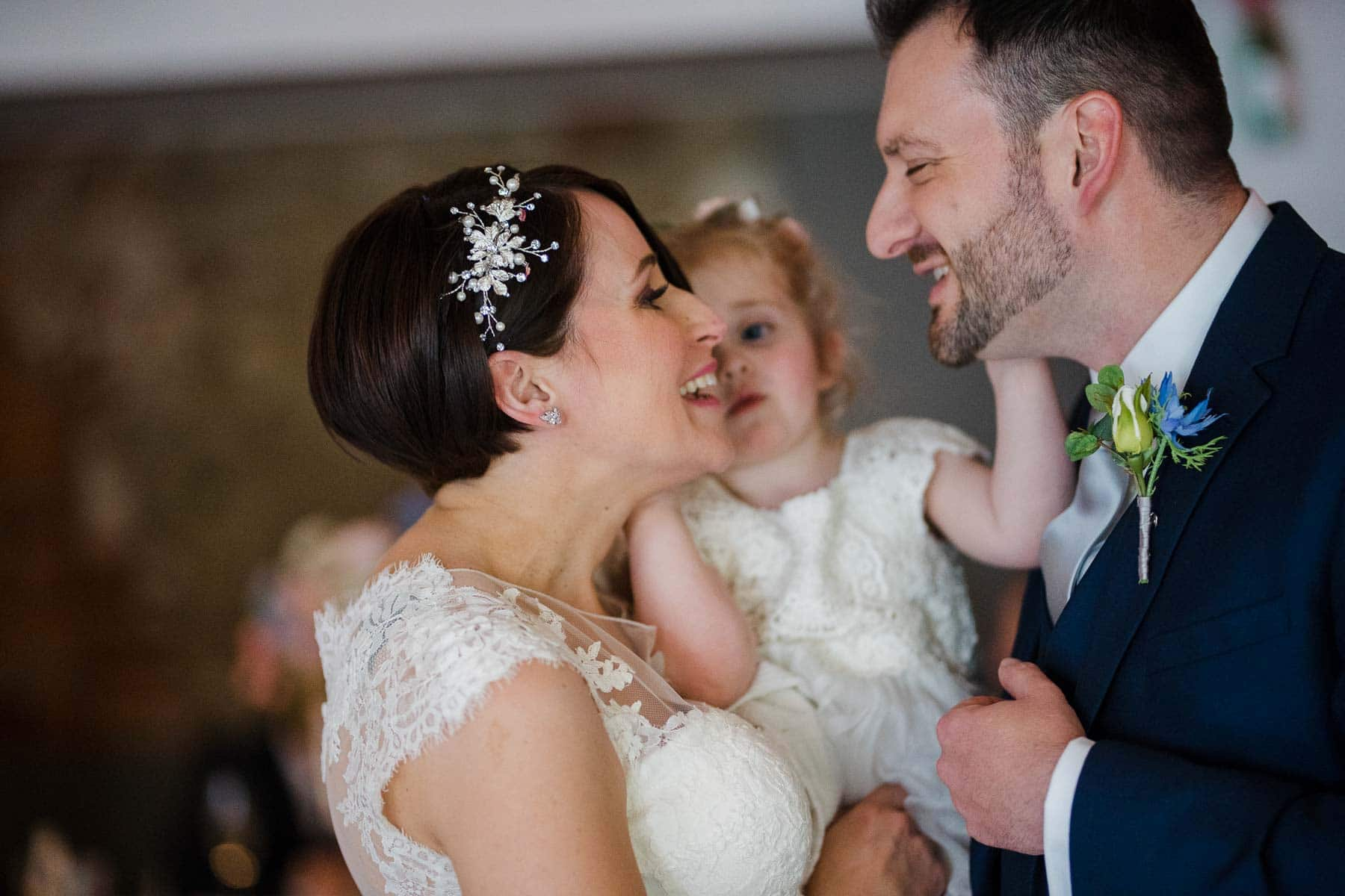 Bride and groom smiling as they are pulled together by daughter for a kiss