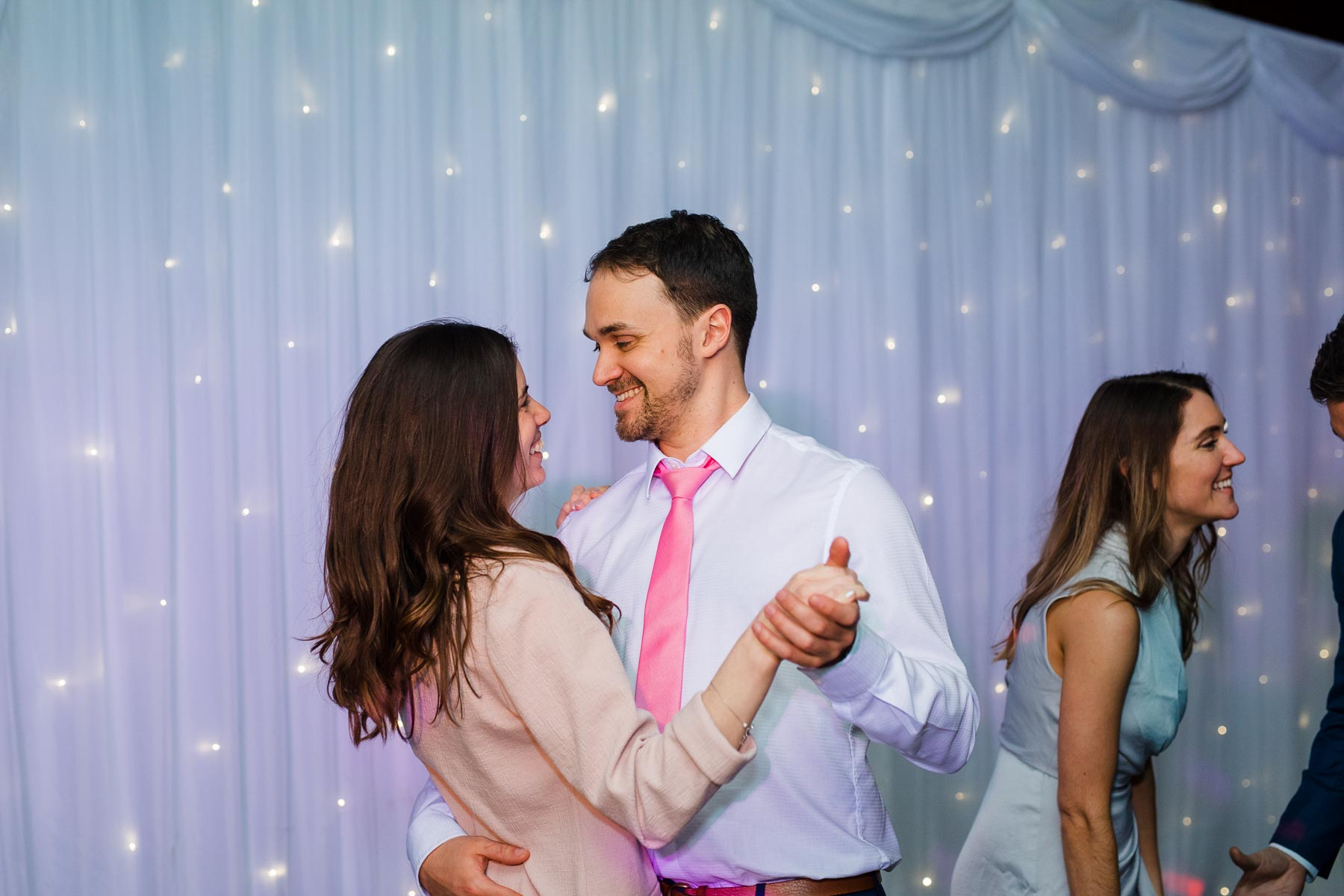 Wedding guests looking dancing romantically on the dance floor
