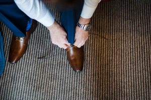 Groom lacing up his shoes getting ready for his ceremony