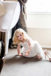 Flower girl putting brides shoes on