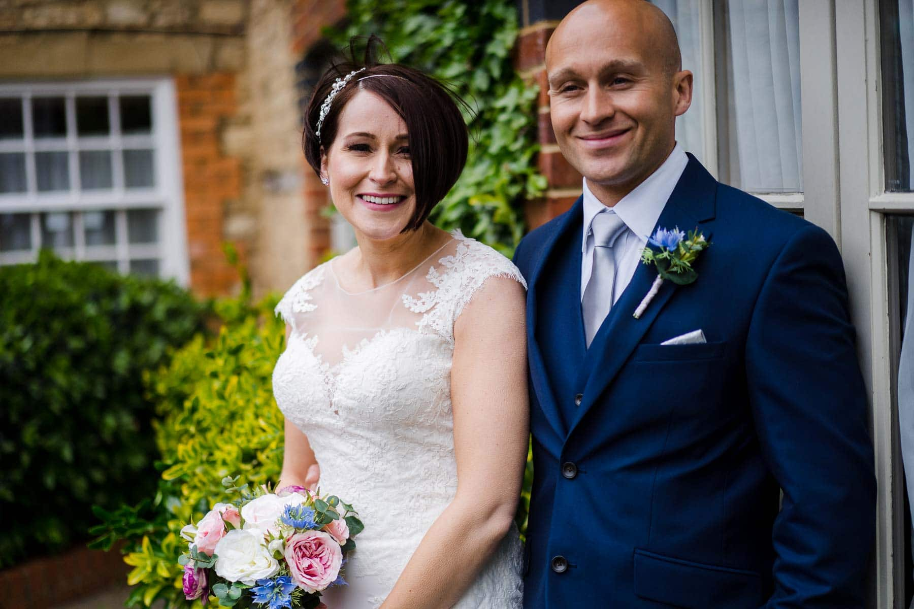 Bride and her brother stand outside in the court yard at The Cock Hotel Stony Stratford