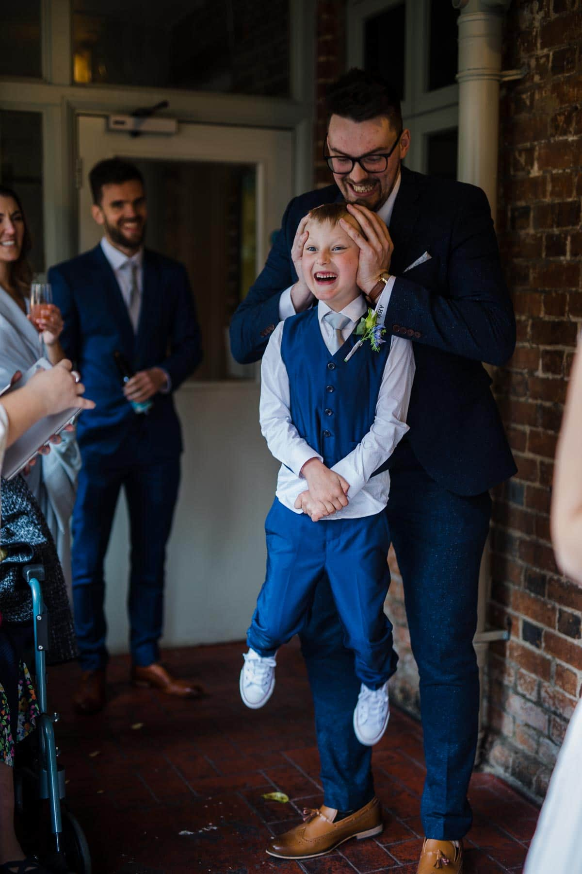 Page boy being picked up by his head in a funny moment before the wedding ceremony