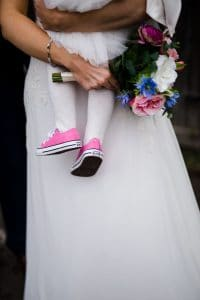 flower girl wearing pink converse shoes matching brides flowers