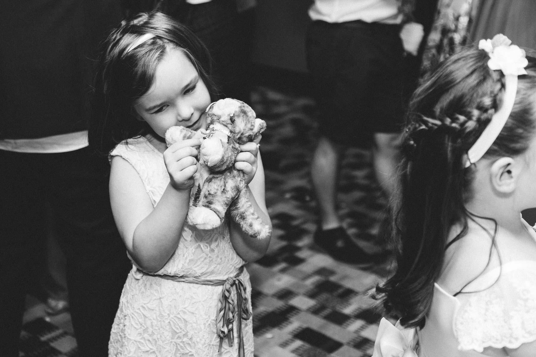 Flower girl holding teddy