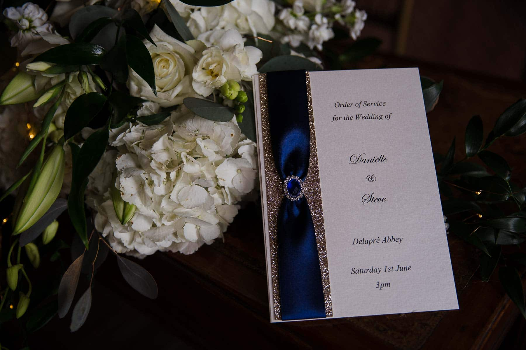Order of service placed next to a bouquet of flowers