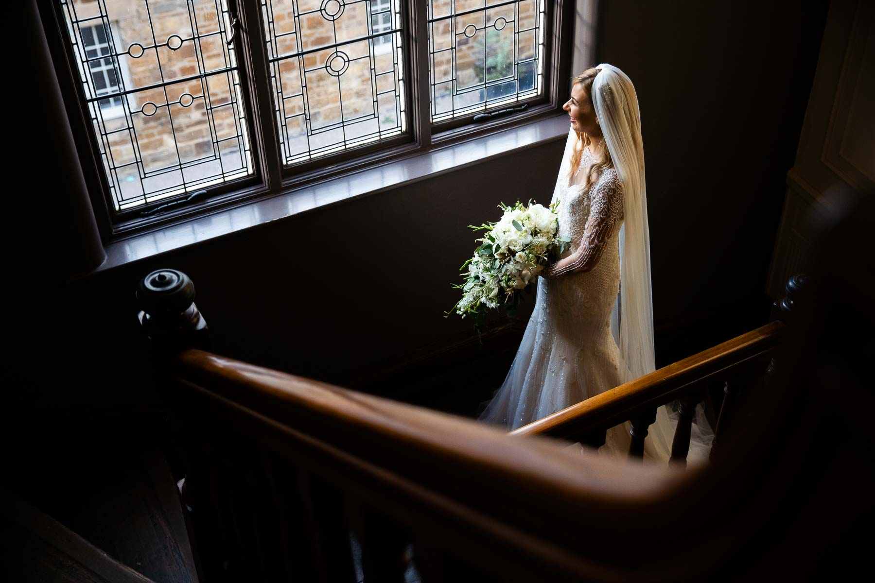 Delapre abbey beautiful stair case, with the bride looking out of the window