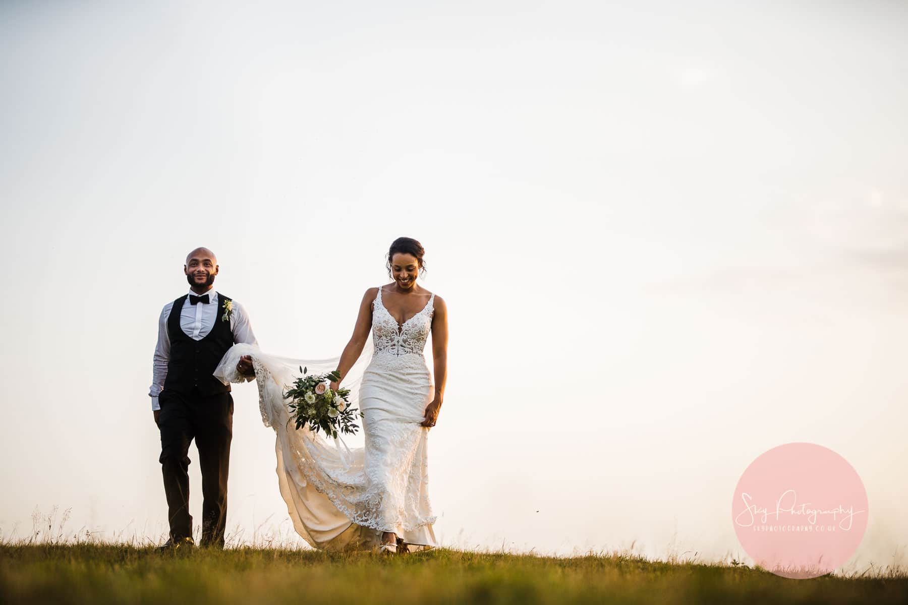 bride and groom walking on dodford manors sheep field