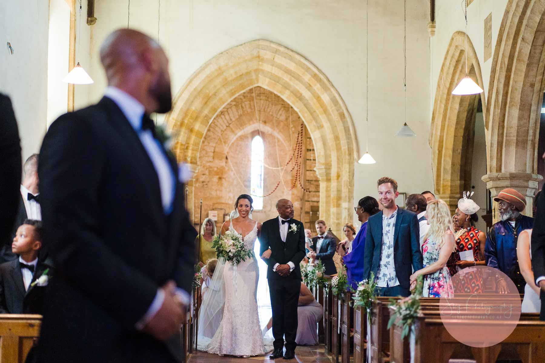 Father and daughter walk down the aisle with an emotional groom looking on