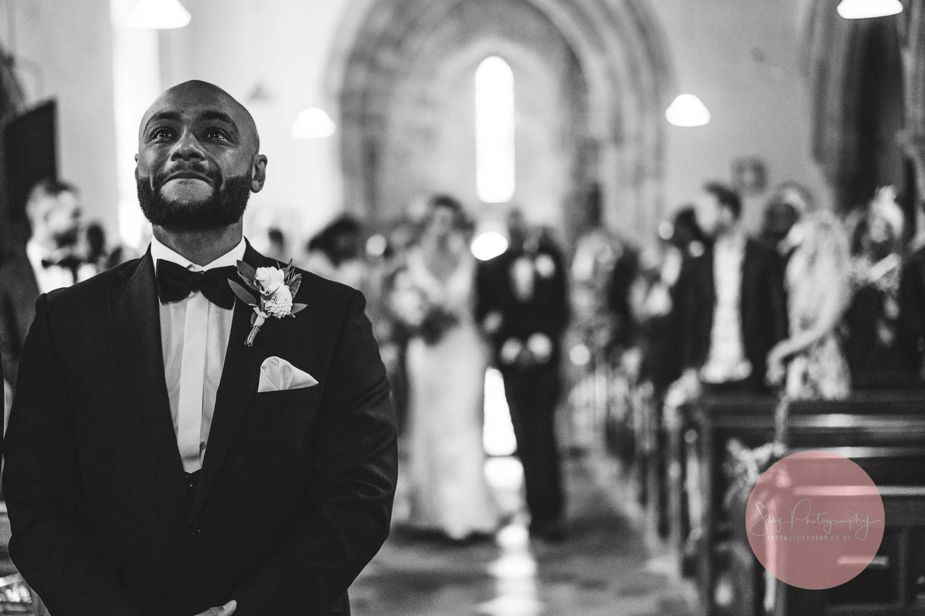 emotional groom in tears as bride comes down the church aisle