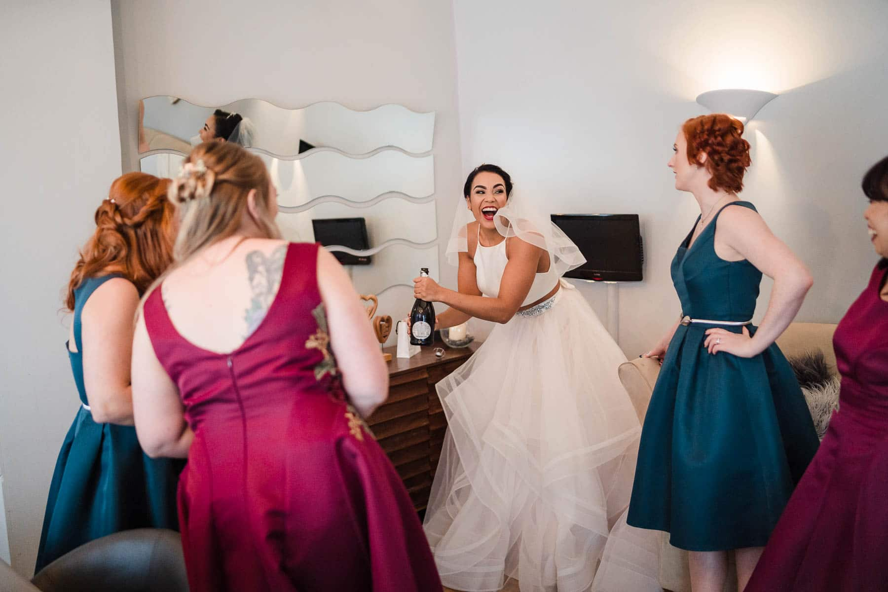 bride popping a bottle of champagne at dodmoor house