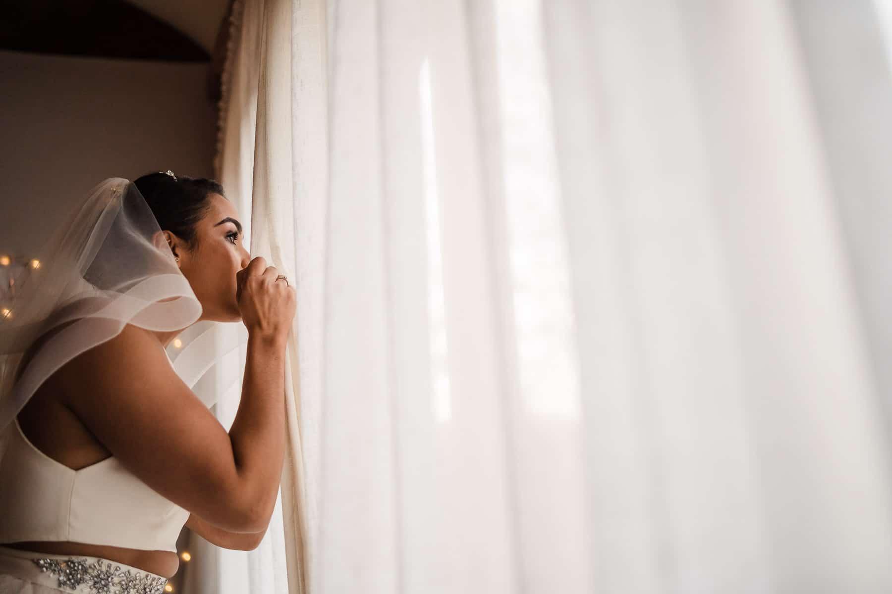 bride taking a sneak peek at her groom through the curtains