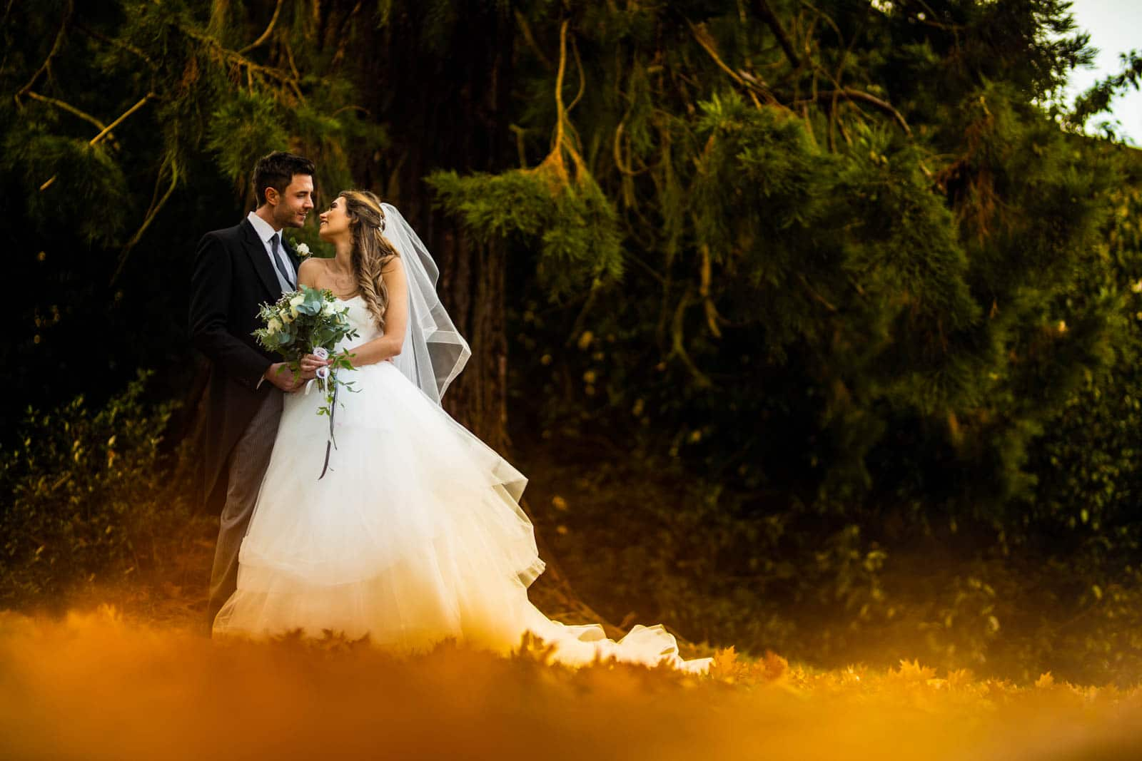 Beautiful autmnal wedding photography of the bride and groom kissing and being surrounded by orange leaves