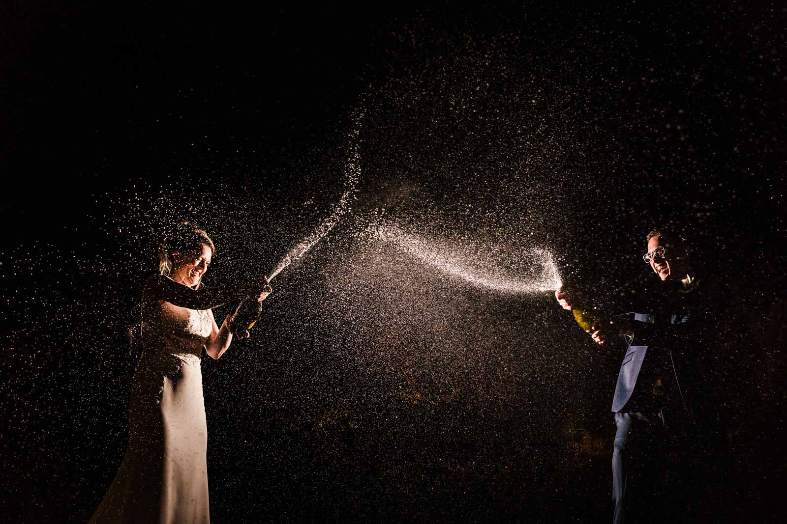 Champagne splash off camera flash photo of couple popping champagne bottle - creative wedding photography