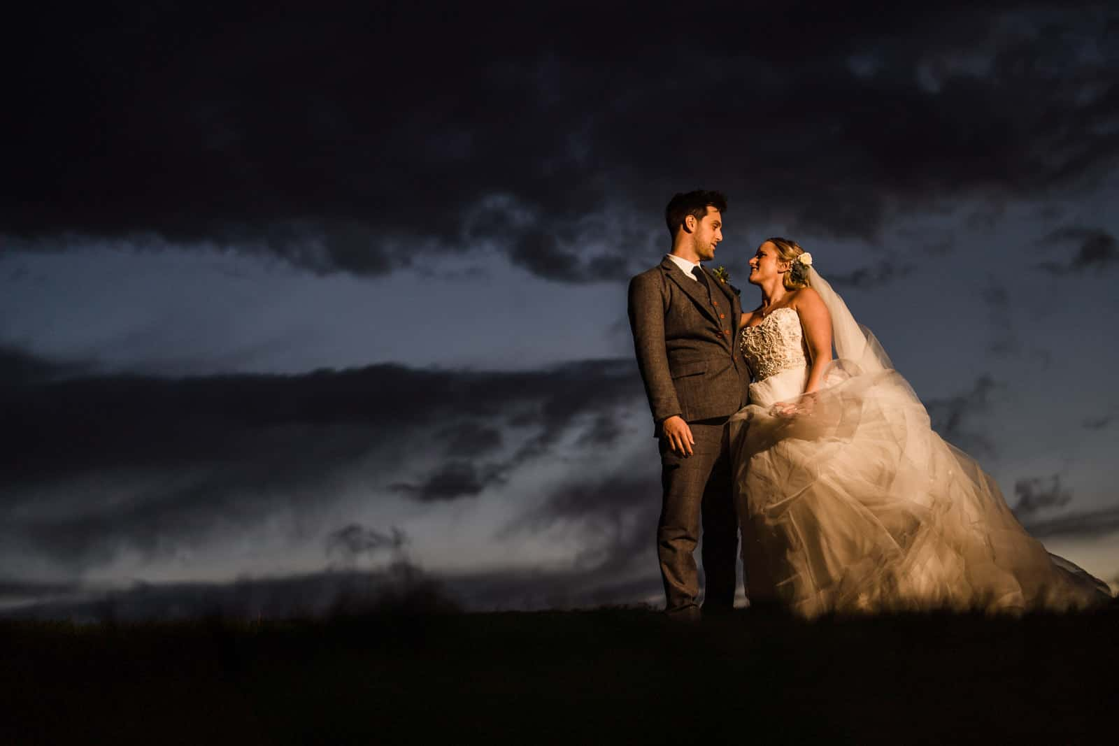 Photo of a wedding couple standing in Dodford Sheep field in evening, External flash used with magmod accessories