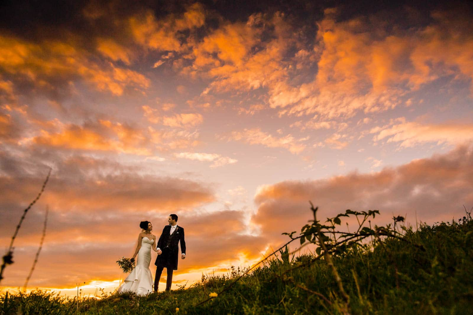 Beautiful colourful sunset sky and the bride and groom walking