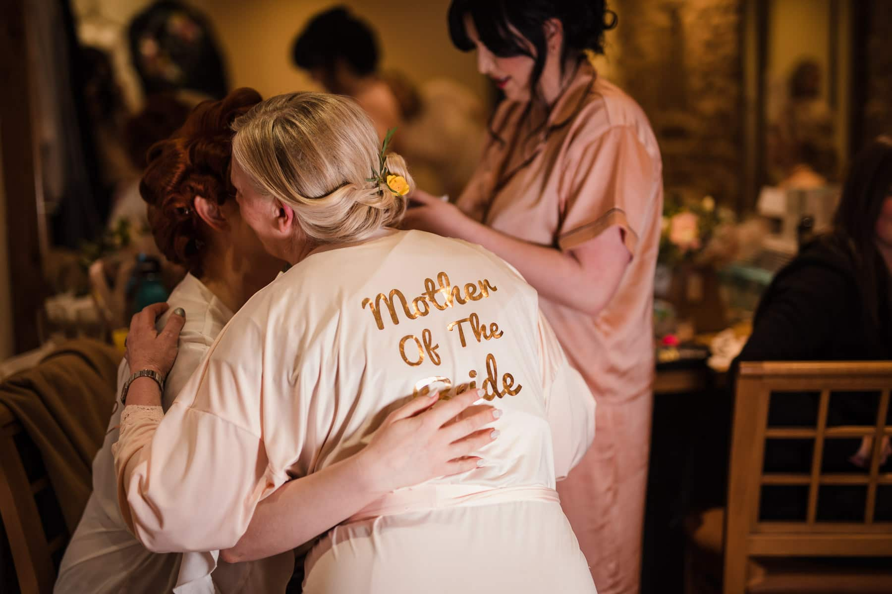 Mother of the bride embraces bride in the bridal room