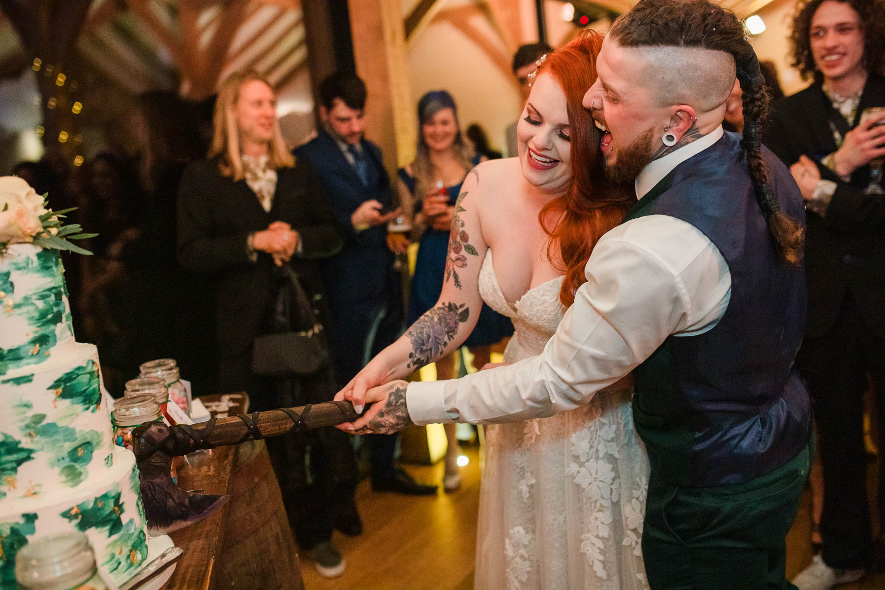 Bride and groom cut cake with Viking Nordic axe