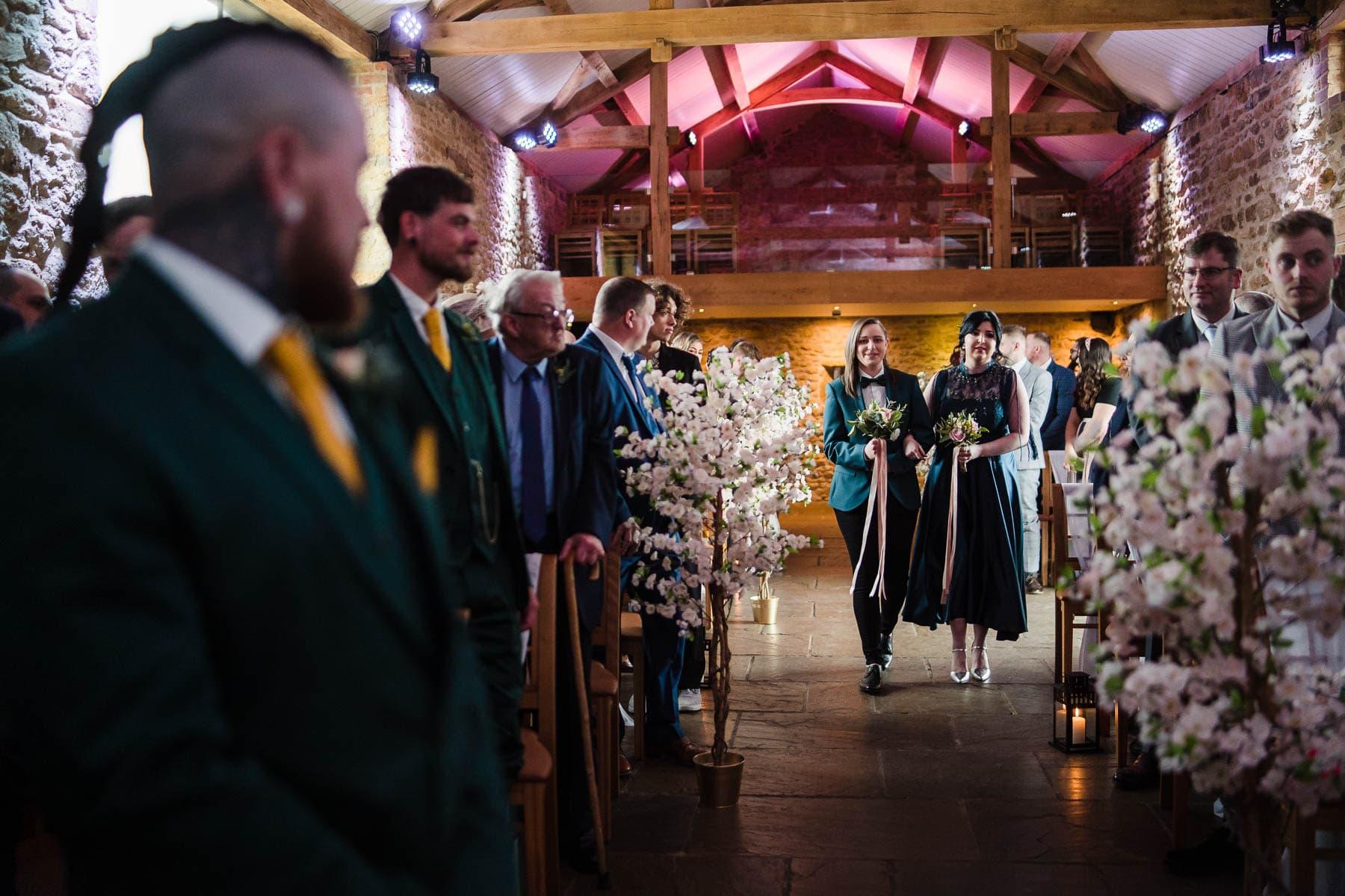 alternative bridesmaids walking down the aisle at dodford manor