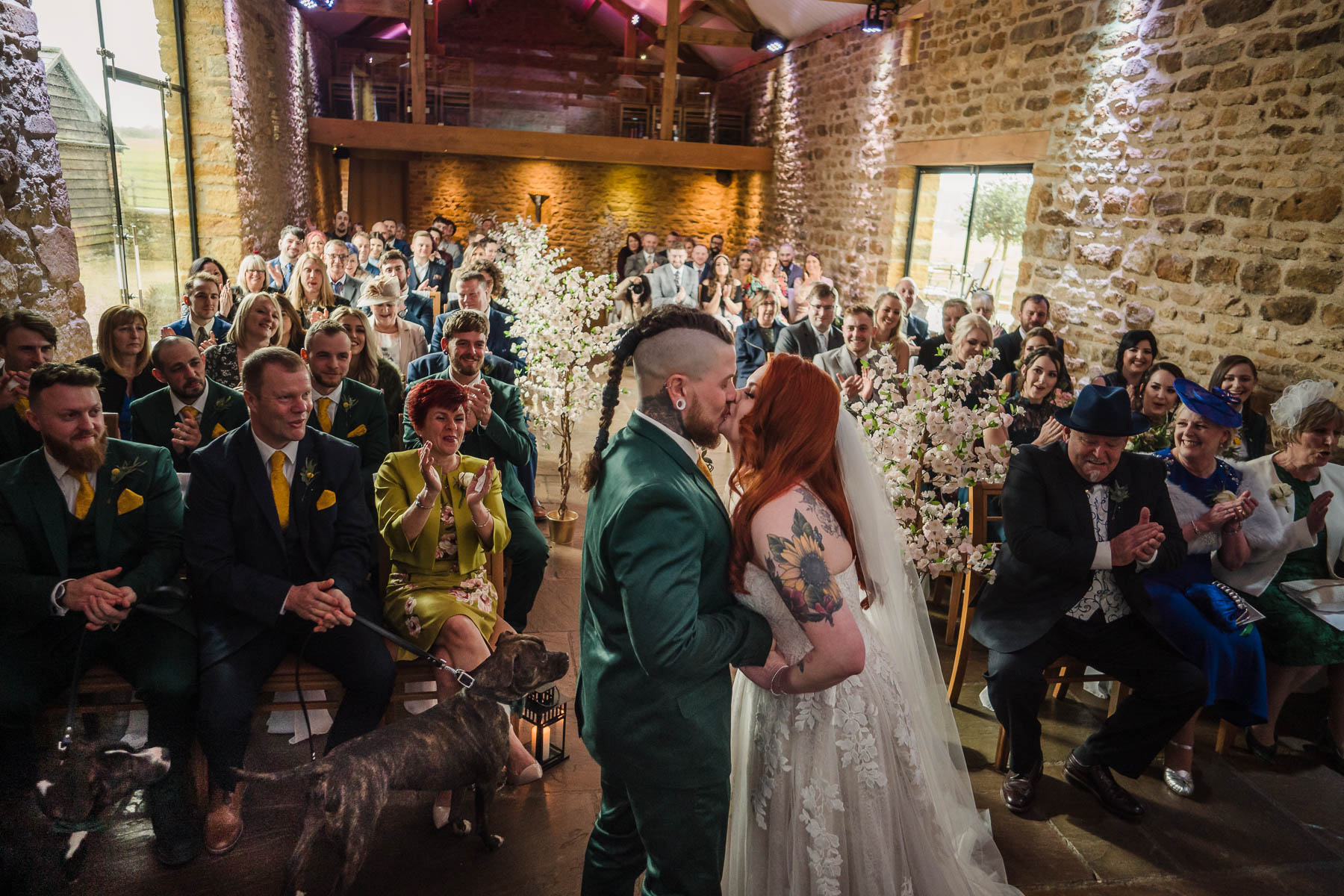 Alternative couple wed in dodford barn in front of guests