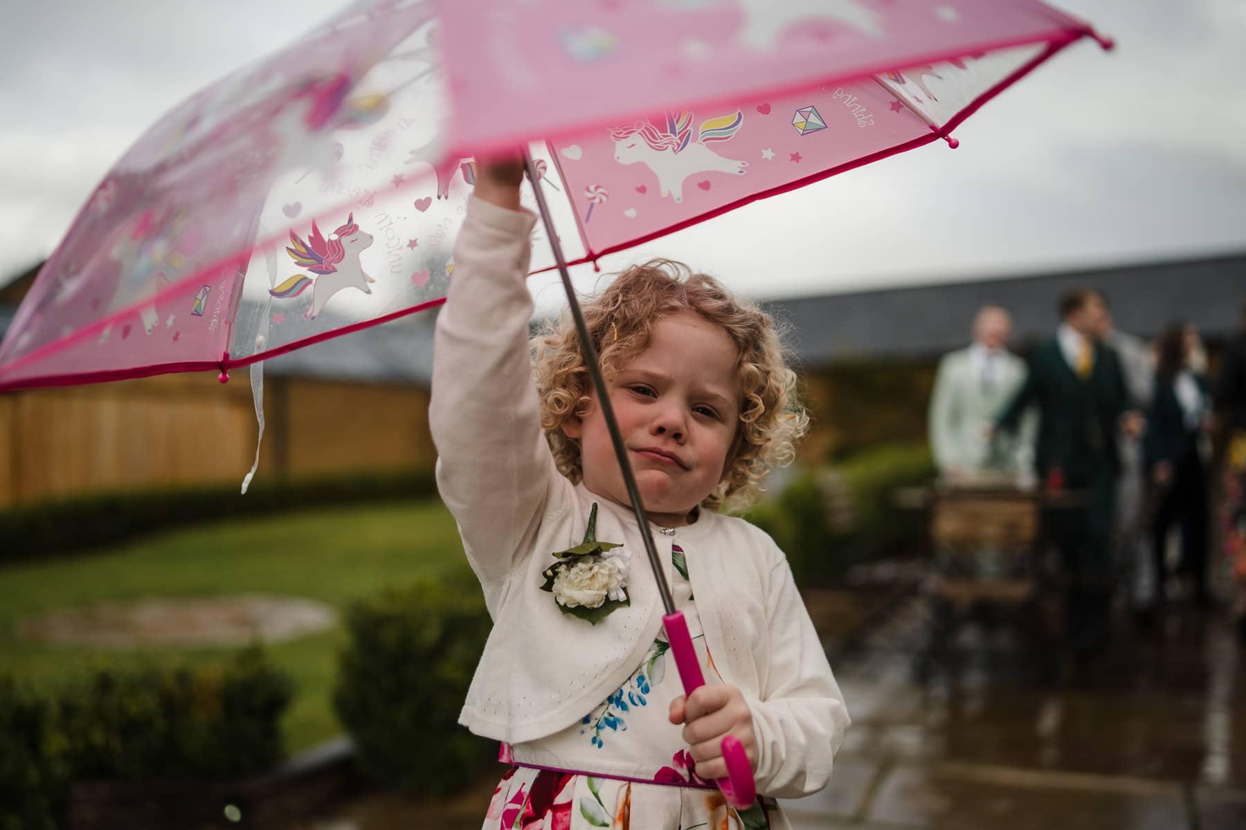 little girl extending umbrella