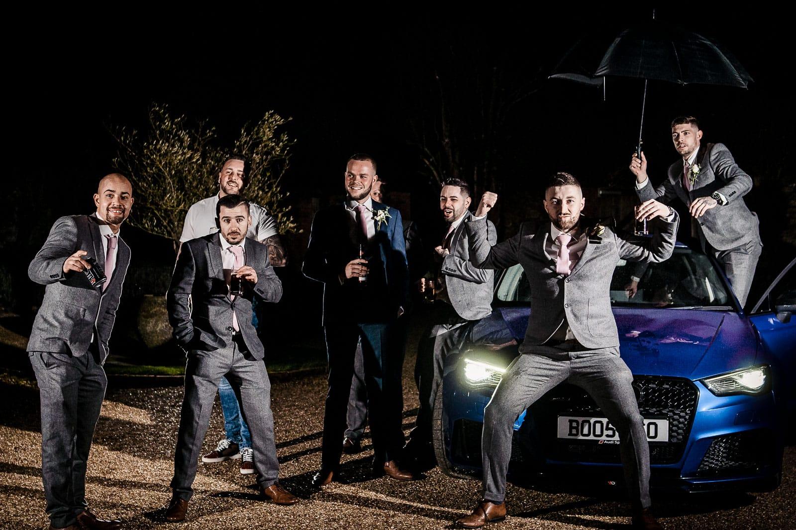 Wedding groomsmen sitting on a car posing