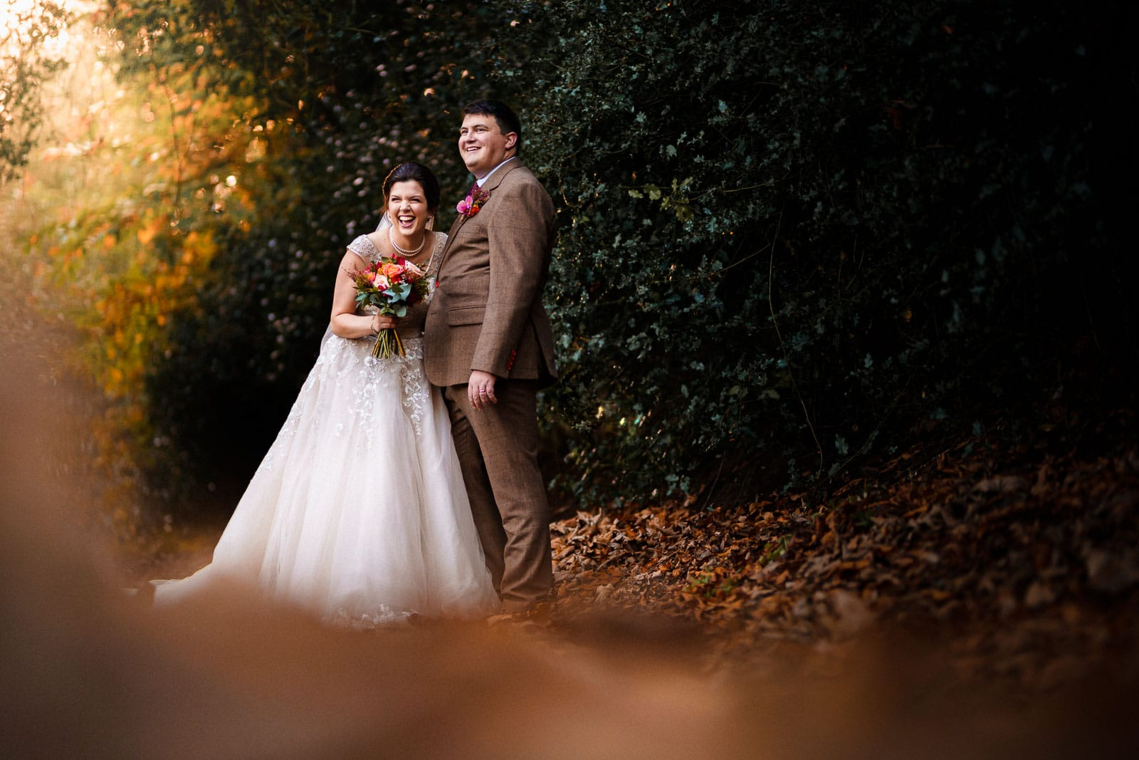 Autumnal wedding scene. Falling leaves and a bride and groom