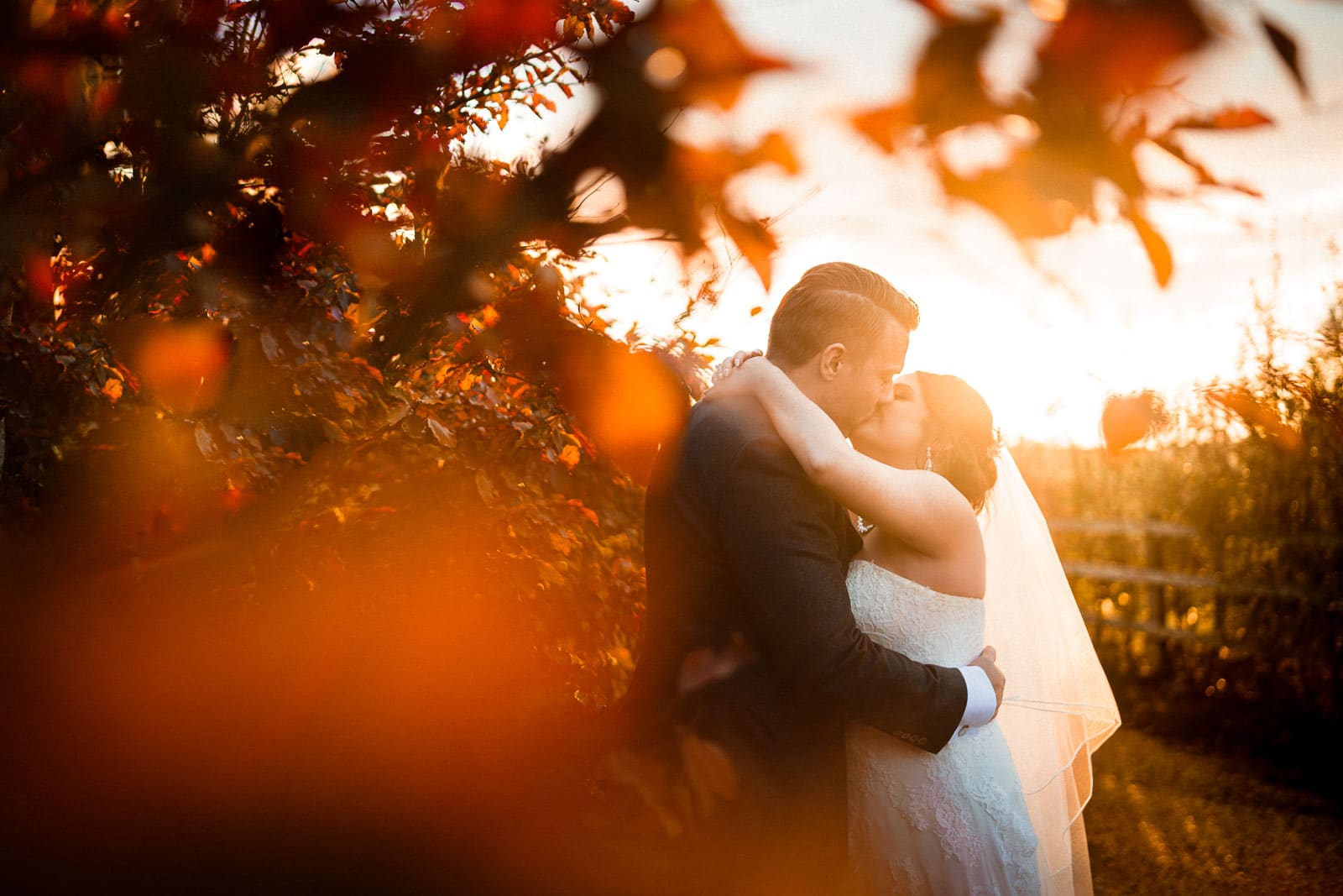 Autumnal wedding photo of a bride and groom kissing