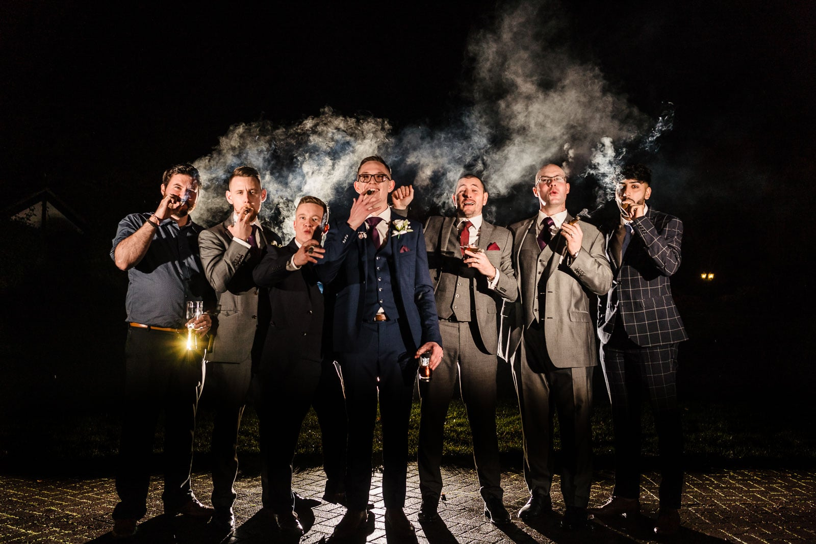 Low light groomsmen cigar photos