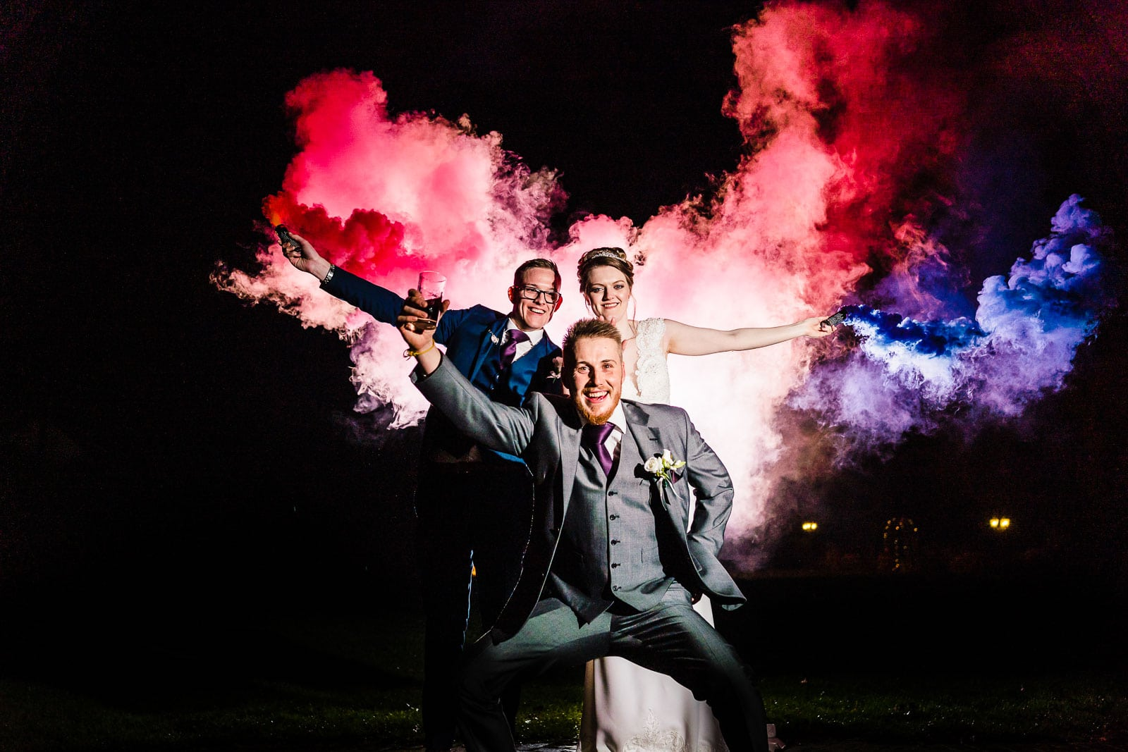 Smoke grenades being used at night by a bride and groom, creative lighting